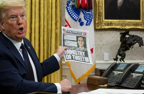 Donald Trump in the White House holds up a copy of the New York Post with a front page about his use of Twitter.
