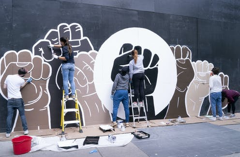 A group of people painting a wall mural