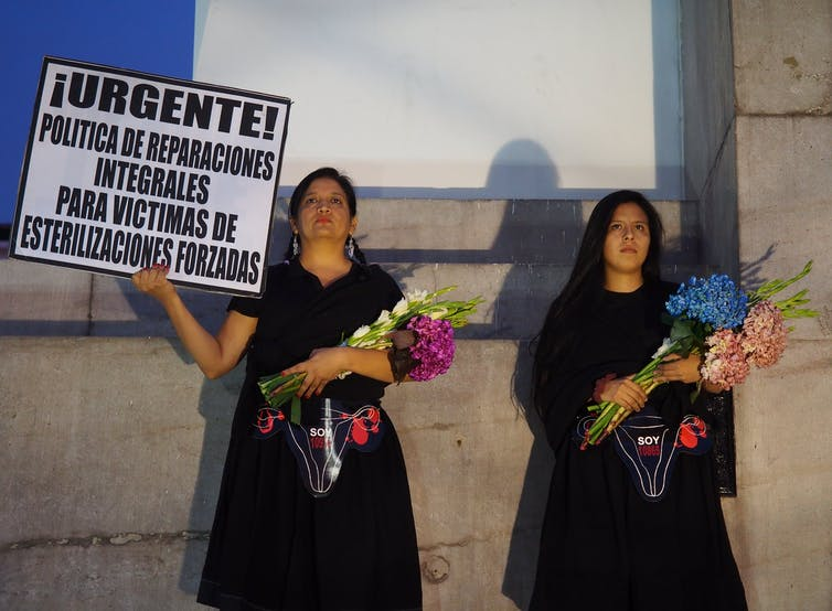 Women in black holding flower bouquets and signs stand solemnly in front of a wall