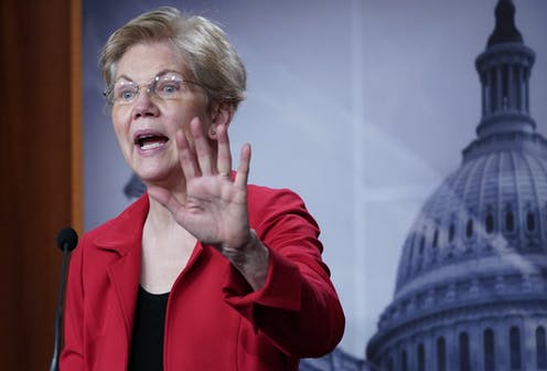 Sen. Elizabeth Warren holds up her left hand as she speaks during a news conference, with an image of the Capitol dome in the background