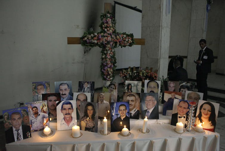 About two dozen photographs displayed on a table with lit candles.