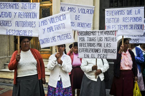 Half a dozen women in Andean dress hold signs decrying forced sterilization on a city street