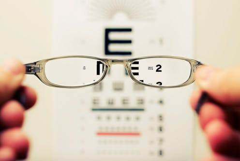 Glasses held in front of a letter chart.