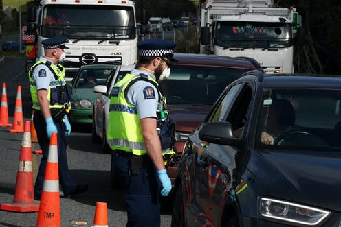 Police officers wearing masks stopping motor vehicles