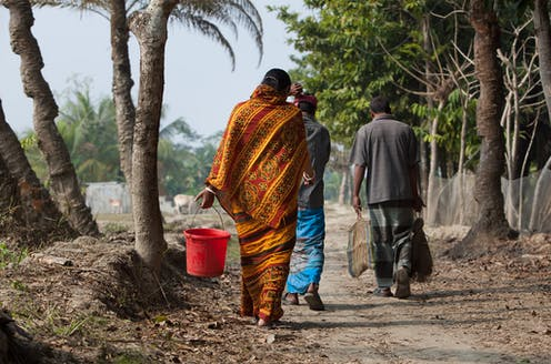 Three people walk on a dirt path by palm trees carrying buckets