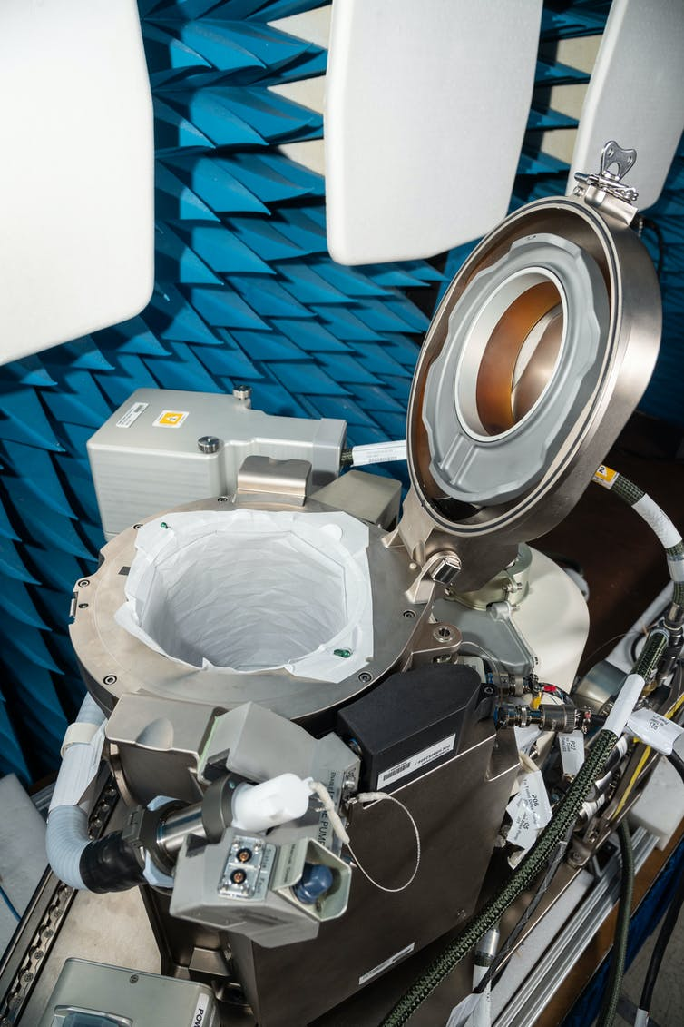 The new NASA Universal Waste Management System has a steel lid, controls and many tubes surrounding the toilet bowl.