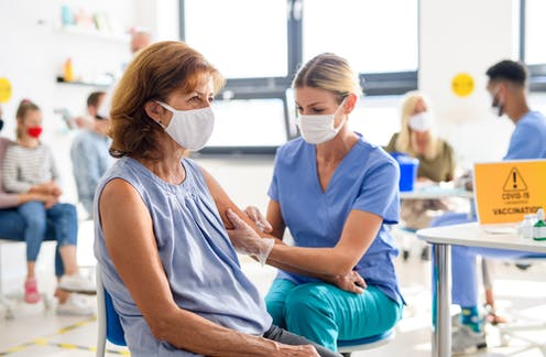 Woman wearing mask getting COVID vaccine