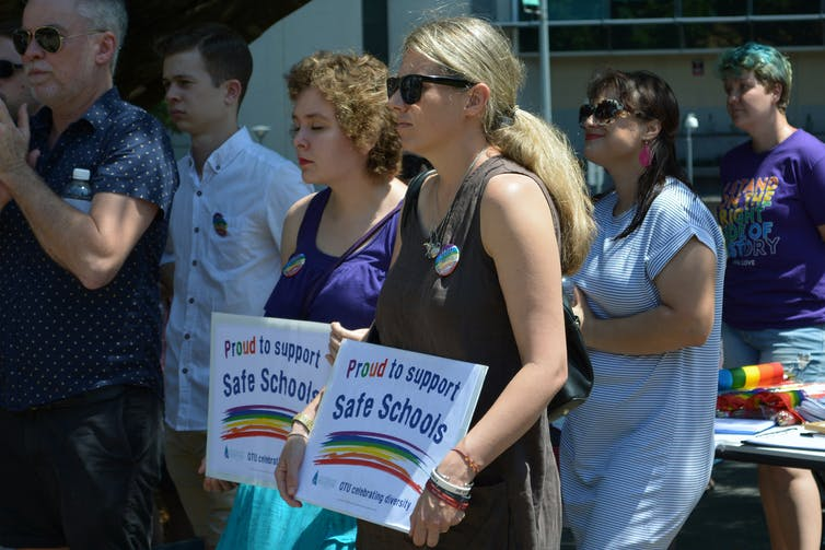 Two women hold signs showing support for Safe Schools program