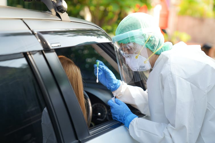 A nurse doing a COVID test for a person in a car.