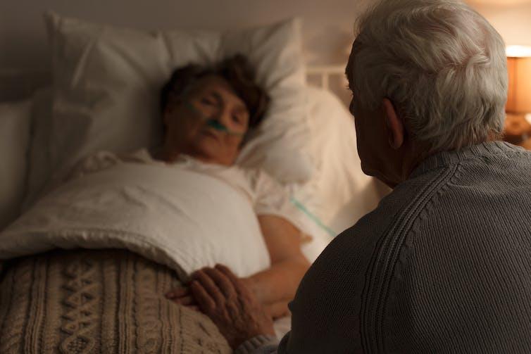 Elderly man holding sick wife's hand