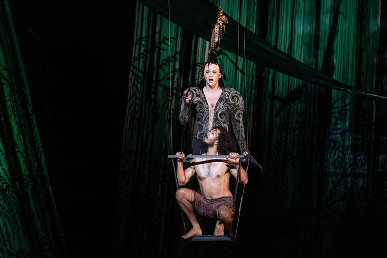 Production image; two men sing on a swing