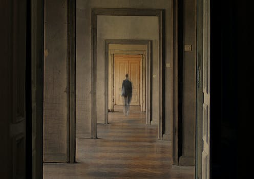 A person seen in the distance through several doorways.