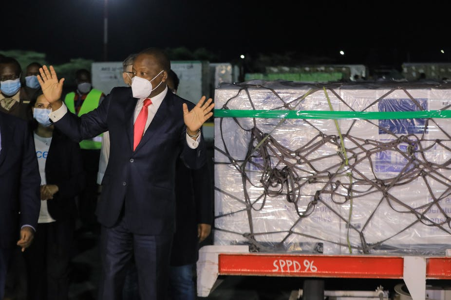 At night, a man in a face mask and a smart suit with a red tie holds his hands up in a pleased gesture, cargo on a trolley behind him.