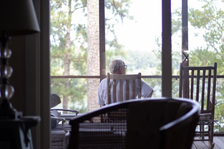 Man sits on chair on balcony looking out at woods