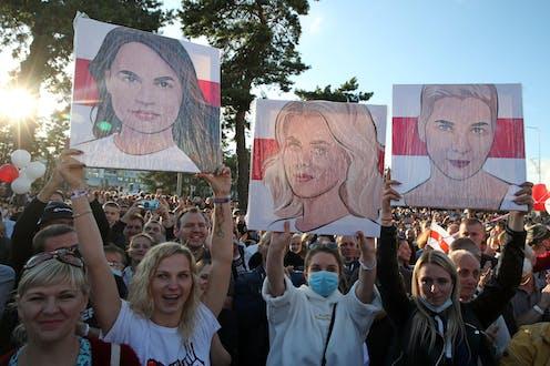 Supporters hold up posters of Belarus opposition figures Svetlana Tikhanovsksaya, Veronika Tsepkalo and Maria Kolesnikova during an election rally in July 2020.