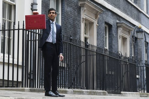 Rishi Sunak holding up the red briefcase outside 11 Downing Street