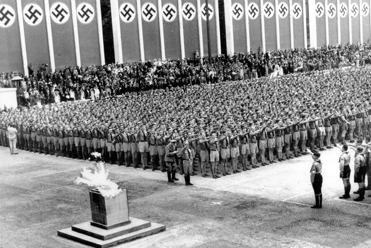 Thousands of soldiers give the Nazi salute while the Olympic flame burns in the foreground.