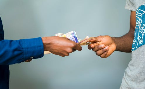 Two hands exchanging money.