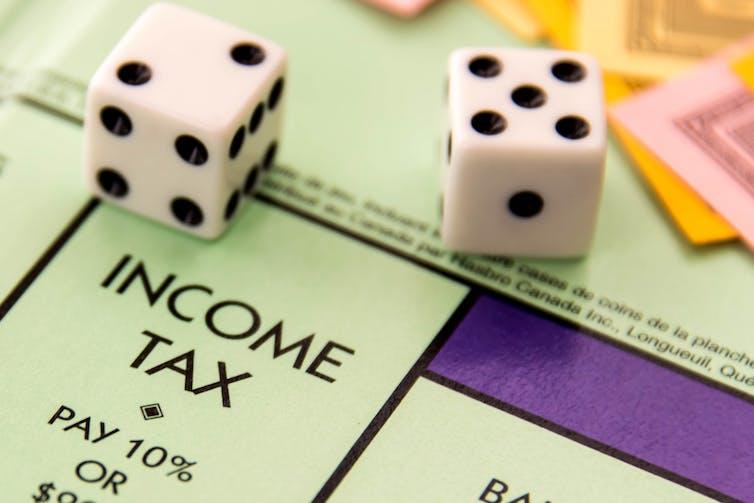 Dice scoring a seven on a Monopoly board above Income Tax square