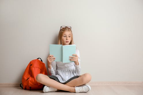 Girl sitting on floor reading a blue book next to orange backpack