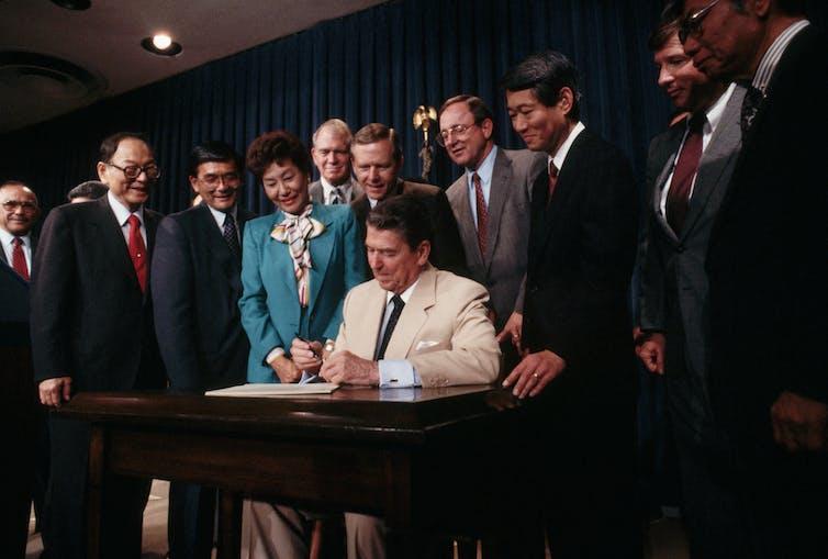 Los congresistas rodean al presidente Ronald Reagan.