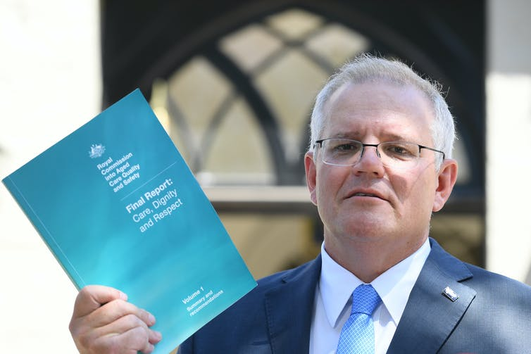 Prime Minister Scott Morrison holding a copy of the royal commission report.