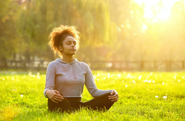 A young woman meditates in a park.