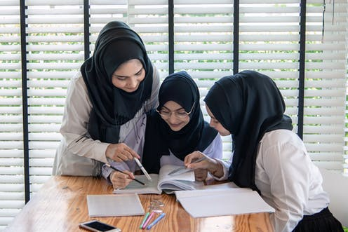 Islamic school girls looking at textbook
