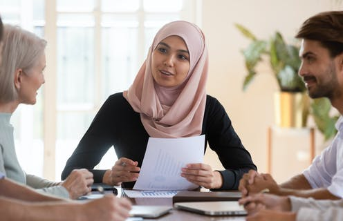 young muslim woman talking with diverse group of colleages