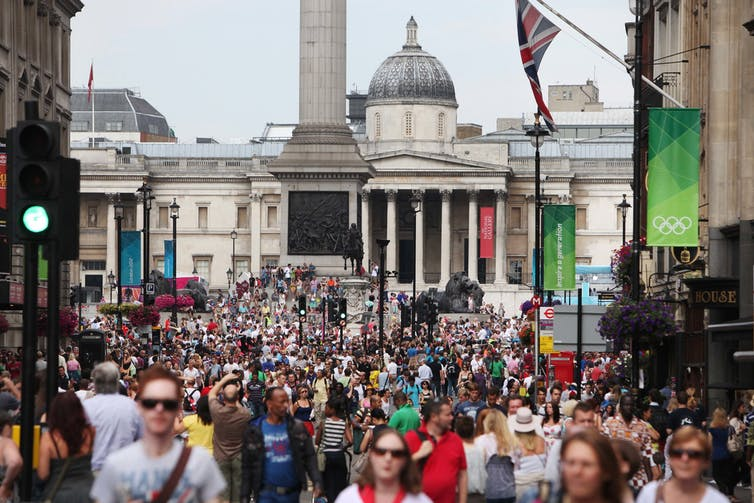 Crowds of people in one of London's busy streets, Olympic banners on buildings and signs,