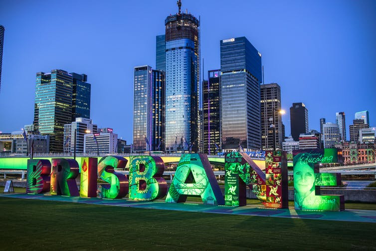 Green lights illuminate the  Brisbane sign at Southbank with the  city scape in the background.