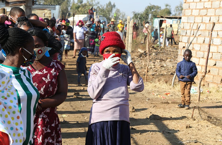 People wearing face masks stand in a line, with shacks in the background