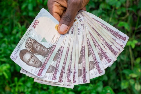 Cropped hand of person holding Nigeria's paper currency
