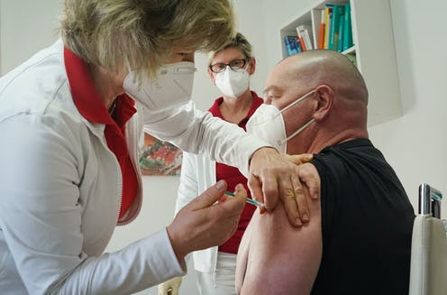A health worker in Germany being vaccinated with the Oxford/AstraZeneca vaccine