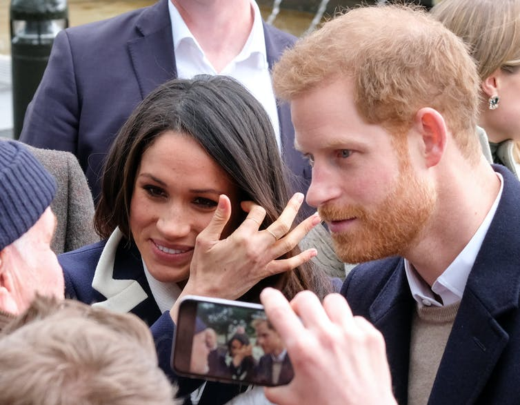 Harry and Meghan are photographed on a smartphone while speaking to a crowd