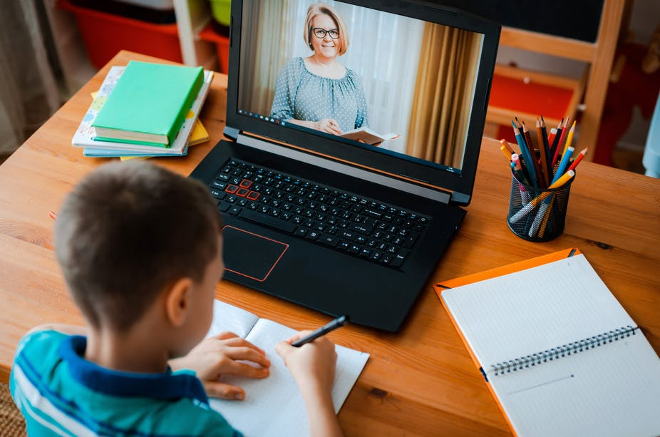 Schoolboy uses laptop to do school work online while watching a livestream of his teacher.