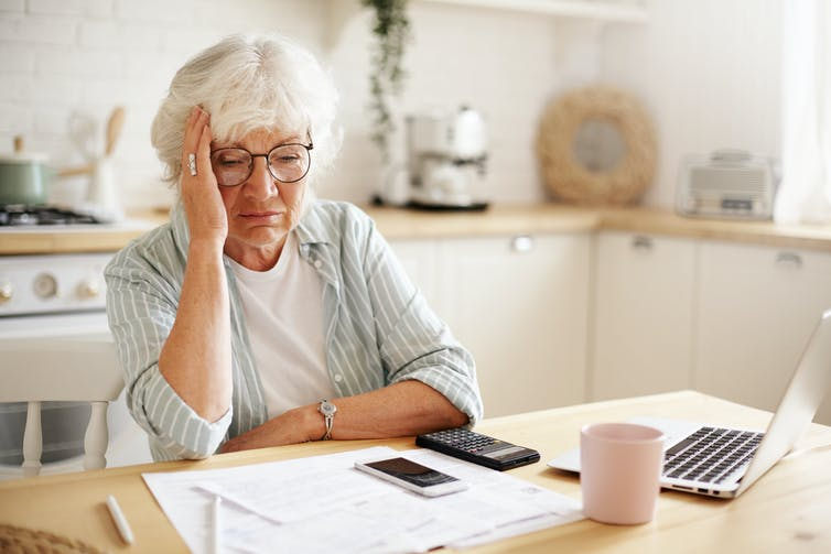 Sad frustrated senior woman holding hand on her face, sitting at kitchen counter with laptop and papers