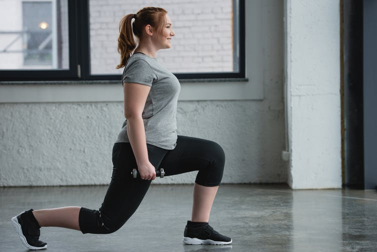 Woman performing lunges while holding dumbbells.