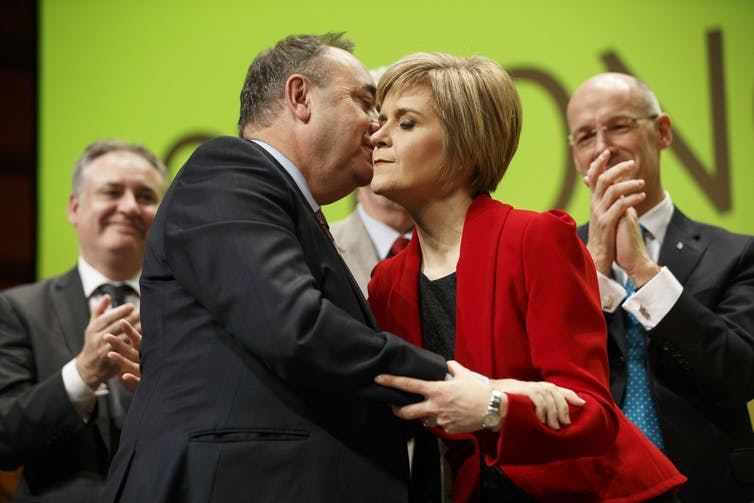 Alex Salmond embraces Nicola Sturgeon surrounded by clapping colleagues.