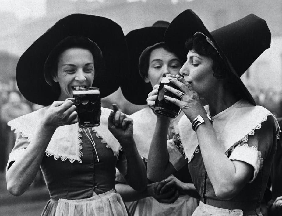 Three women wearing tall hats smile and sip from mugs of beer.