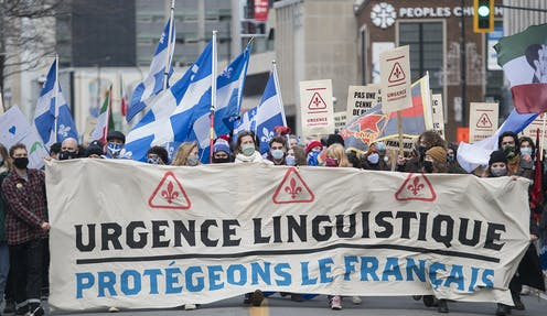 French-language rights protesters carry a banner that reads Urgence Linguistique and carry fleur de lis flags.