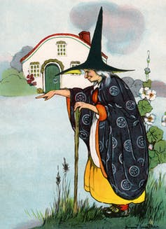A witch, hunched over and wearing a tall, pointy hat, casts a spell.