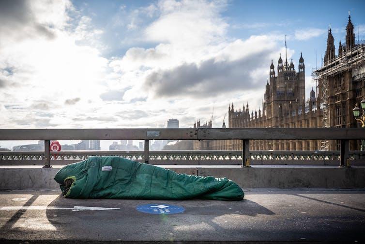 Rough sleeper in sleeping bag on Westminster bridge, London.