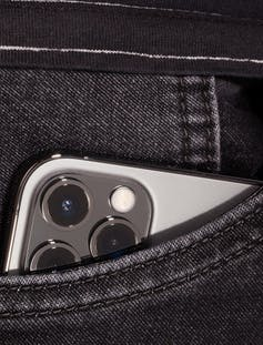 An iphone in a jeans pocket