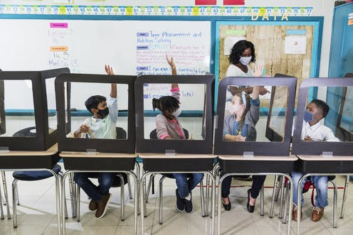 A teacher wearing a mask calls on her students who are sitting in desks with plastic shields.