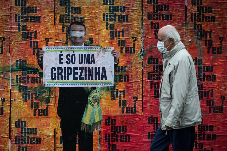 A man in a mask walks next to an image of Brazilian President Jair Bolsonaro holding a sign with his comment about COVID-19 at the beginning of the pandemic, 'It's just a little flu,'