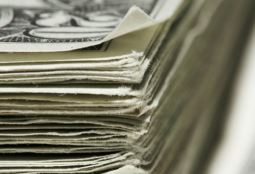 A closeup of stack of 20 dollar bills.