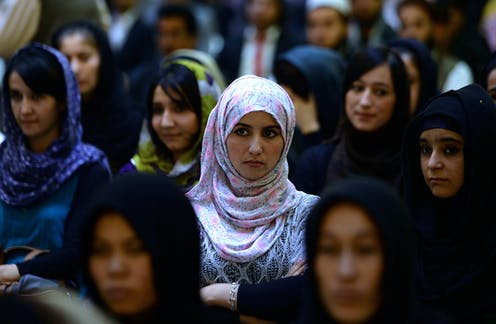 Women, most in hijab, stand in a crowd and listen attentively.