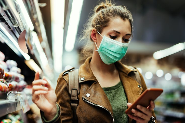 A woman wearing a mask looks at her smartphone.