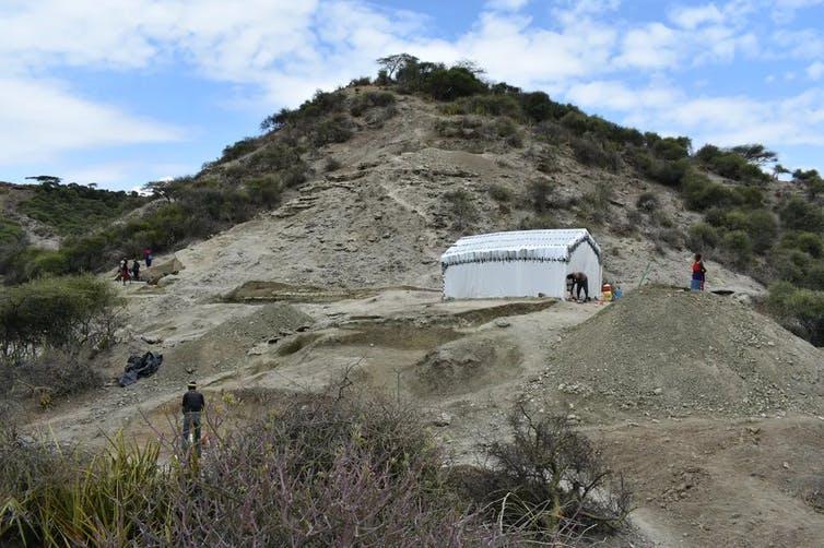Archaeologists working next to a tent on a hillside.